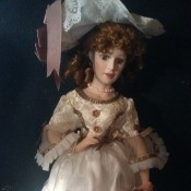 Value of an Ashley Belle Doll - doll wearing a large lace trimmed hat and a dress with lace bodice and white skirt with bows