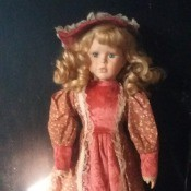 Value of a Porcelain Doll - doll in salmon colored dress and hat