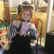 Value of a Porcelain Doll  - doll wearing a period dress, long skirt, striped puffy sleeves, and a lacy bodice