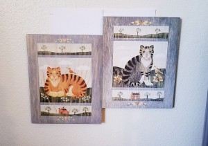 Two cat pictures in frames.
