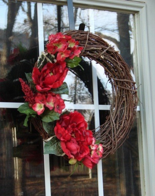 A grapevine wreath decorated with red flowers