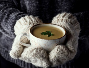 A pair of mittened hands holding a cup of soup.