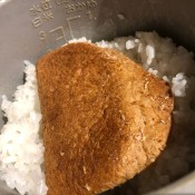 A piece of bread in a pot of mushy rice.