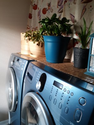 A table runner on top of a washer and dryer.