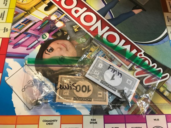 A Monopoly board game with the pieces saved in sandwich bags.