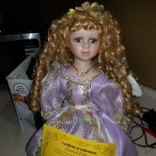 Value of a Knightsbridge Collection Porcelain Doll - doll with long curls wearing a lavender dress