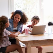 A mom and kids around the computer.