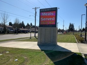 Picking Up Free School Lunch During COVID-19 Closures - school sign with times for meals