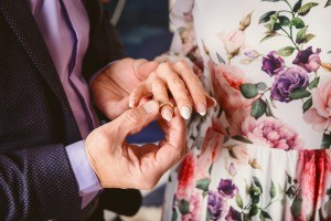 A man placing a ring on the hand of a woman.