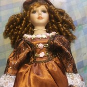 Value of an Ashley Belle Doll - doll with ringlets, bronze dress with white lace trim