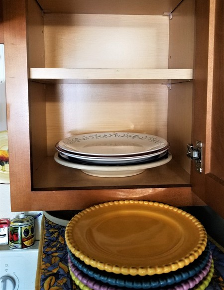 A cupboard with plates on the lower half.