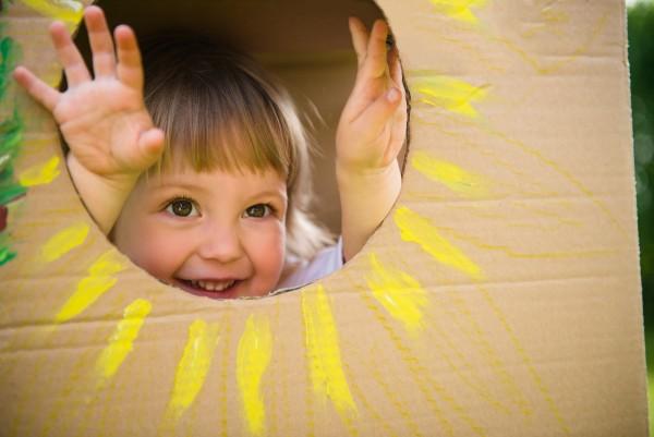 A child looking through a sun in a cardboard box.
