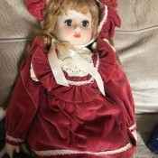 Identifying a Porcelain Doll - doll wearing a red velvet dress and matching hat