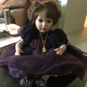 Identifying a Porcelain Doll - sitting doll wearing a dark purple dress and gold chain with a heart shaped pendant