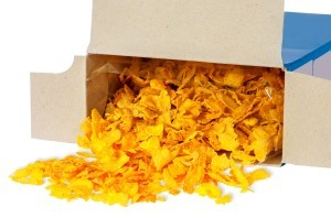 A cardboard cereal box with corn flakes spilling out.