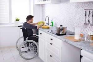 A man in a wheelchair doing the dishes.