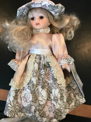 Value of a Cathay Collection Doll  - doll wearing a peach and gray and white floral dress