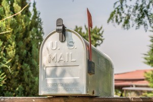 A metal mailbox in front of a house.