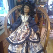 Value of a Collector's Choice Doll by Dandee - doll wearing a floral tiered dress, standing on a chair
