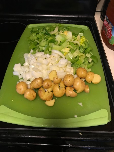 Celery, onion and potatoes chopped on a cutting board.