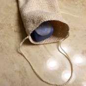 Crocheted Exfoliating Soap Sack - sack with a piece of soap inside lying on the bathroom counter
