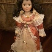 Identifying a Porcelain Doll - doll wearing a dark pink satin dress with white lace trim