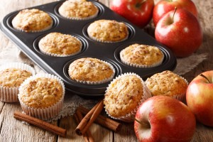 A muffin tin with apple cinnamon muffins inside, next to apples and cinnamon sticks.