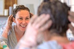 Woman dying her hair at home looking into a mirror.