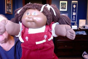 Selling a Cabbage Patch Doll - brown skinned girl Cabbage Patch doll wearing red overalls and a white shirt