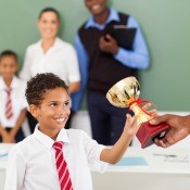 A student receiving a trophy at school.