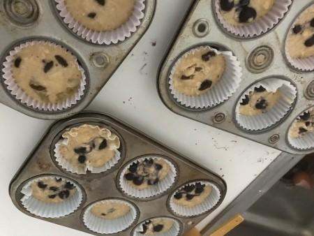 adding raisins to Muffin tins
