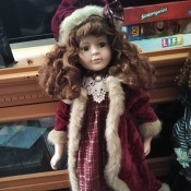 Value of a Collectors Choice Porcelain Doll - doll wearing a long plaid dress with a white fur trimmed coat and matching hat