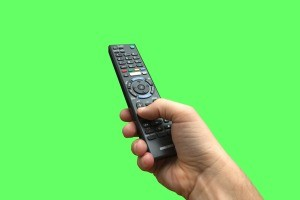 A remote control on a green background.