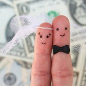 Two fingers decorated as a bride and groom with a background of dollar bills.