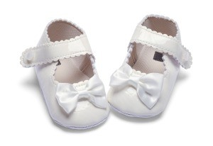 A white pair of baby shoes.