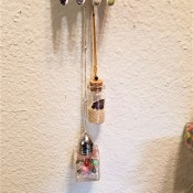 Two decorative glass bottles hanging below artwork.