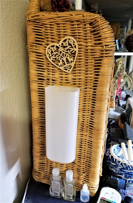 A plastic container attached to the side of a small wicker shelf.