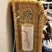 Eyeglasses hanging on a plastic container attached to the side of a small wicker shelf.