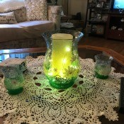 A flameless candle inside a green flowered vase.