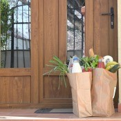 Two bags of groceries delivered on the front porch of a house.