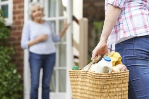 A woman delivering a shopping basket full of groceries to a neighbor.