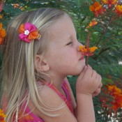 A girl smelling a colorful flower.