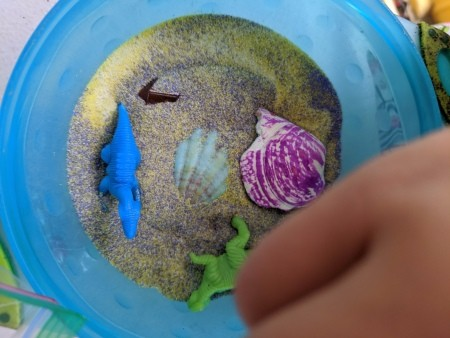 Making a Sand Terrarium or Fairy Garden for Kids - blue bowl with sand, shells, and plastic diosaurs
