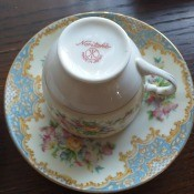 Value of Noritake China - upside down cup on a heavily decorated saucer with blue and brown design around the edge and clusters of pink flowers in three areas in between
