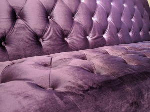 A couch upholstered in purple velvet.