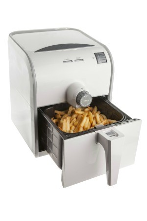 An electric air fryer with French fries.