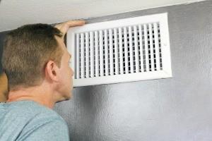 A man looking at an air vent.