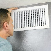 A man looking at an air vent.