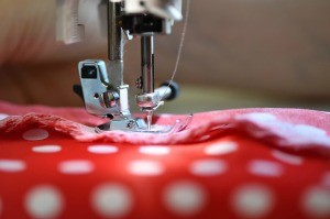 A sewing machine needle sewing a seam in red and white polka dotted fabric.
