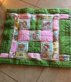 I Never Promised You a Rose Garden (Quilt) - finished quilt on a tile floor